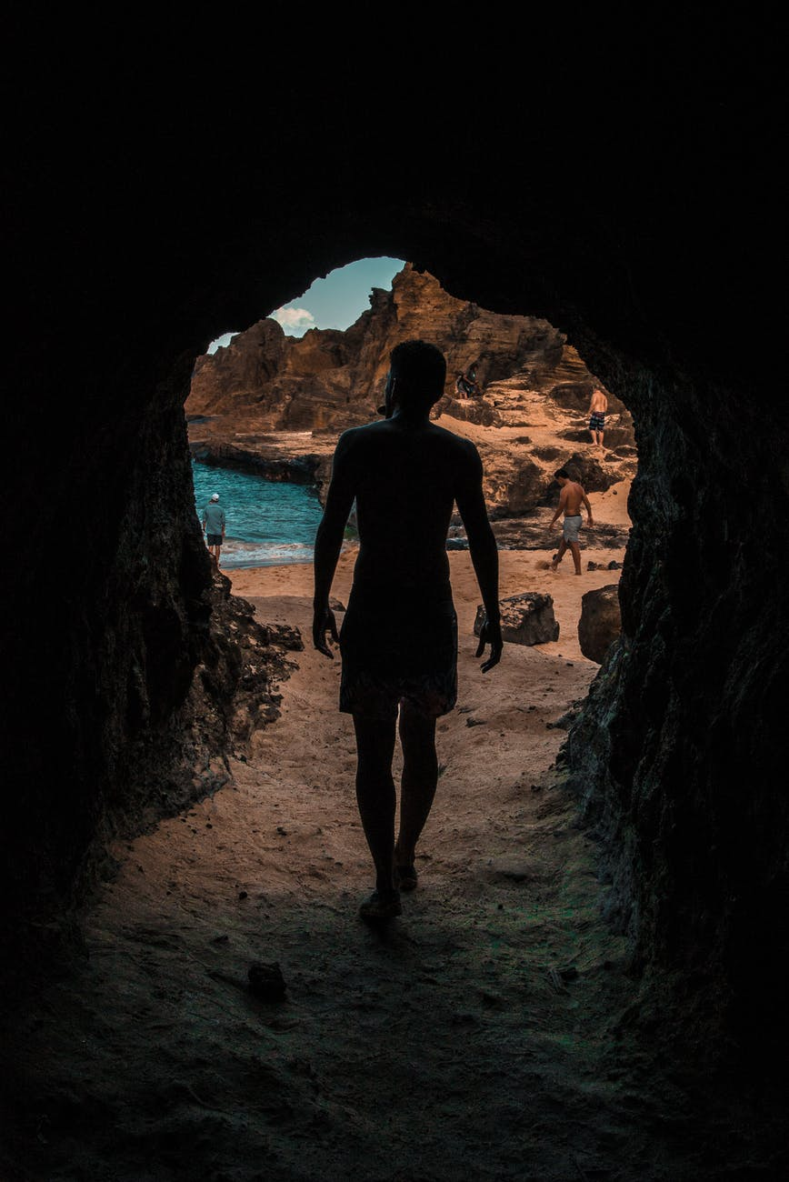back view photo of person walking out of a cave